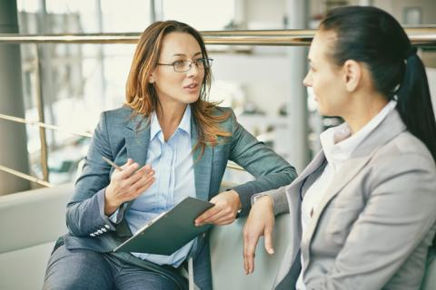 Two business women discuss salary during a job interview